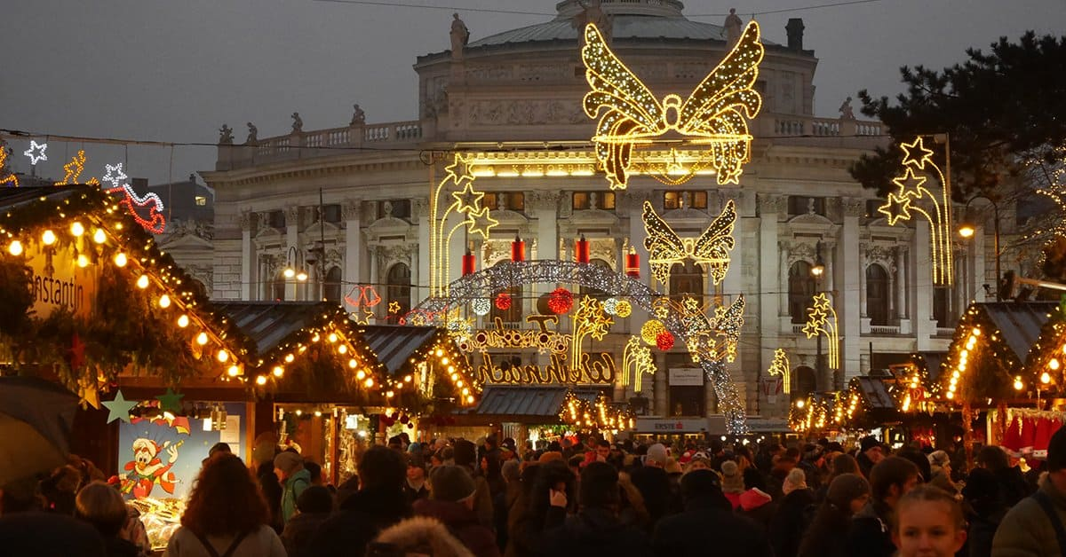 Photograph of a Christmas market in Vienna with crowds of people, Christmas lights, booths that sell crafts and a large, stone building in the background.
