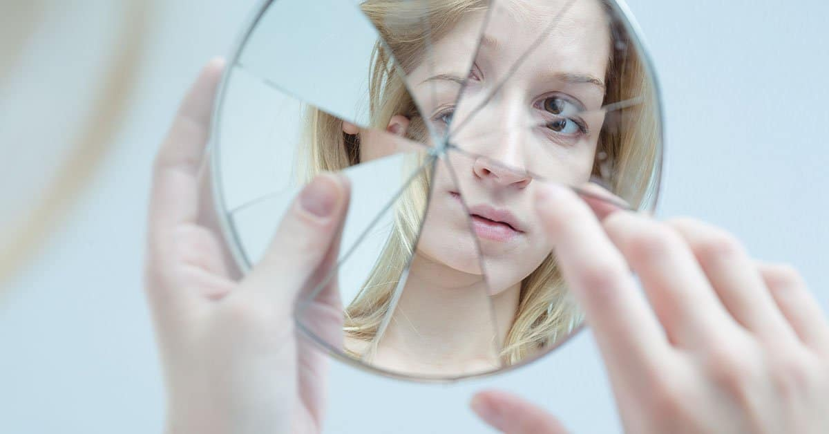 Change resistance: Female face reflected in a broken mirror.