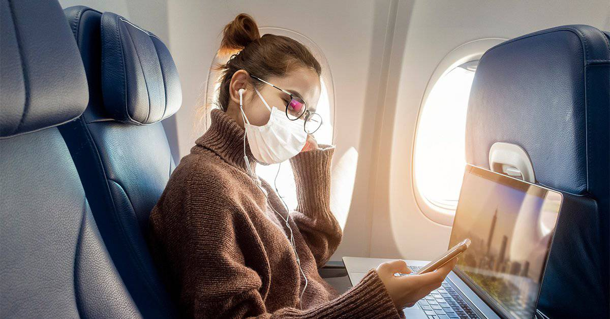 Business person sitting on an airplane looking at her phone with her laptop open.